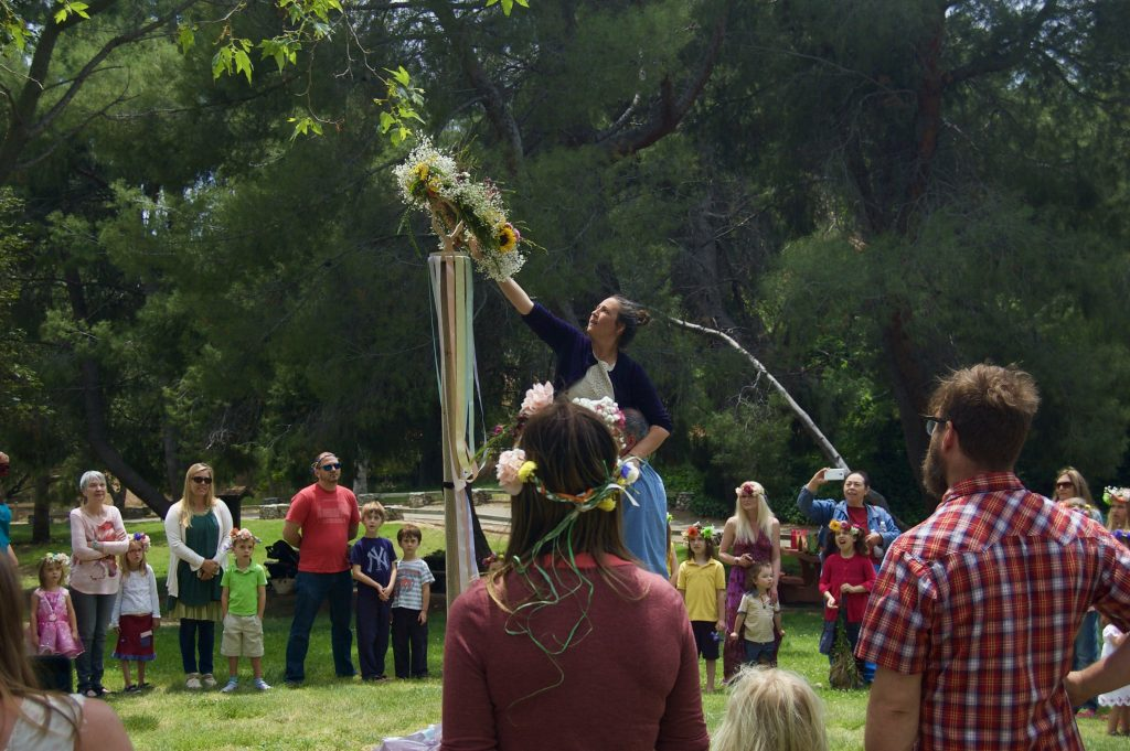 Crowning the Maypole with a handmade wreath!