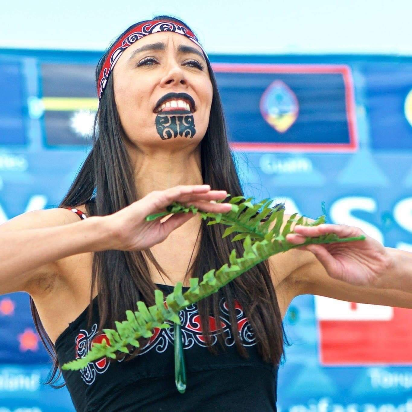 Amelia Butler with traditional Maori face painting, elbows out, with greenery in her hands.